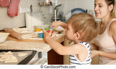 4k footage of cute toddler boy helping his mother cooking and making dough on kitchen