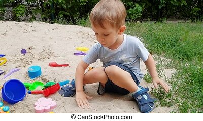 4k footage of cute toddler boy playing in the sandbox on...