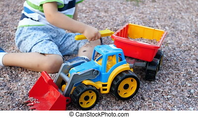 4k footage of cute toddler boy playing with toy tractor and trailer on playground