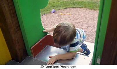 4k footage of cute toddler boy trying to climb on high slide at playground