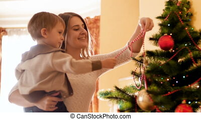 4k footage of cute toddler boy with mother decorating...