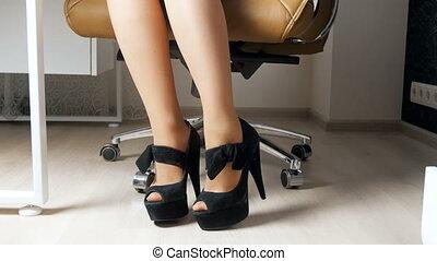 4k footage of elegant businesswoman wearing long heels sitting in office chair