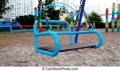 4k footage of empty colorful swings on playground at...