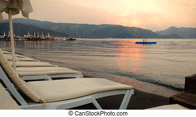 4k footage of empty sunbeds and calm sea water at sunset -...