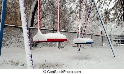 4k footage of empty swings on playground covered in snow...