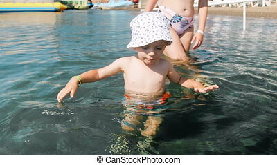 4k footage of funny toddler boy in hat walking in cold sea water at sunny day