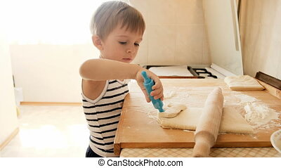 4k footage of funny toddler boy learning making pie on...