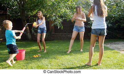 4k footage of happy family having fun on grass at backyard and shooting with water from toy guns