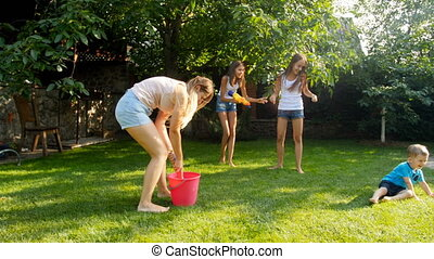 4k footage of happy laughing young family playing with plastic toy water guns at backyard