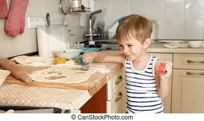 4k footage of happy smiling toddler boy playing with dough on kitchen while making cookies