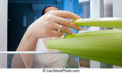 4k footage of happy smiling woman taking celery from refrigerator at night. Concept of dieting