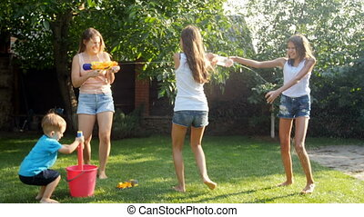 4k footage of happy young family playing with water guns on...