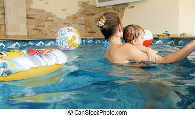 4k footage of happy young family with children swimmming in indoor swimming pool at house