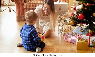 4k footage of happy young mother giving her 3 years old toddler boy Christmas gift in box at morning