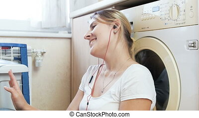 4k footage of happy young woman listening music in headphones while clothes washing in machine at laundry