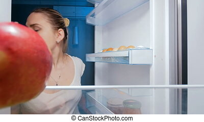 4k footage of hungry young woman sneking in fridge and...