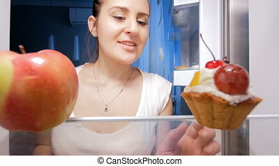 4k footage of hungry young woman taking red apple instead of cake from refrigerator at night. Concept of dieting