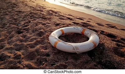 4k footage of life buoy ring lying on the beach at sunset -...