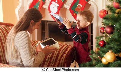 4k footage of little boy giving present to his mother on Christmas morning. Family giving and receiving New Year presents in living room next to Christmas tree.