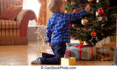 4k footage of little boy sitting on floor at living room and decorating Christmas tree with baubles and balls. Family decorating house on winter holidays and celebrations.