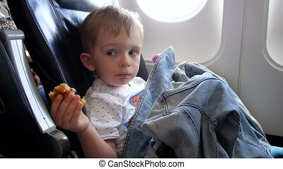 4k video of little boy sitting on passenger airplane seat and eating during flight