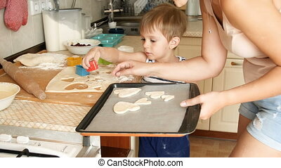 4k footage of little boy with mother making cookies from...