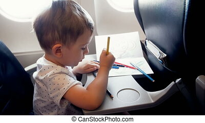 4k footage of little smiling boy drawing on passenger seat at aircraft during flight
