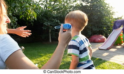 4k footage of little toddler boy blowing soap bubbles with family on grass at backyard