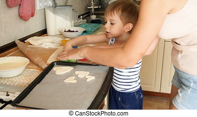 4k footage of little toddler boy cutting dough for cookies...