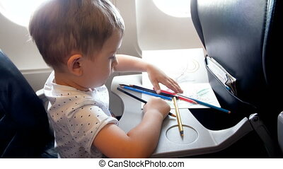 4k footage of little toddler boy drawing with colorful pencil on folding table at airplane during flight