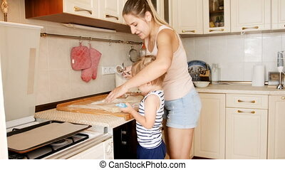 4k footage of little toddler boy helping his mother cutting...