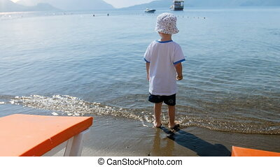 4k footage of little toddler boy throwing stone in calm sea on beach