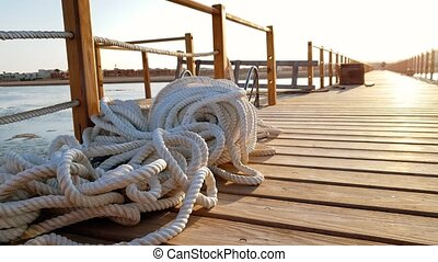 4k footage of long wooden pier at sunset rays. WHite ropes...