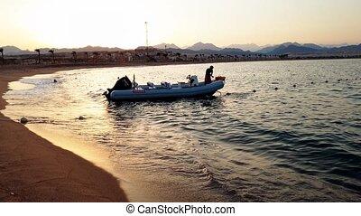 4k footage of motorboat on calm sesa waves at sunset light -...