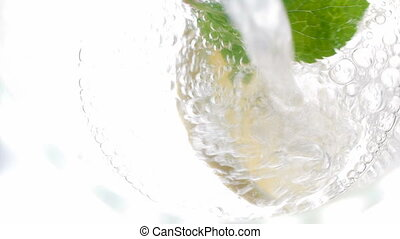 4k footage of pouring cold water in jar with cut lemons,...