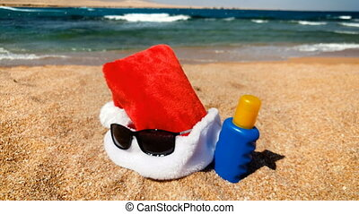 4k footage of Santa hat lying on the sandy beach. Concept of...
