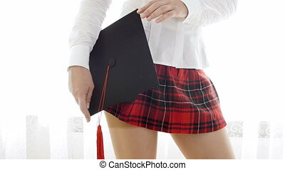4k footage of sexy student girl in short red skirt holding mortarboard cap