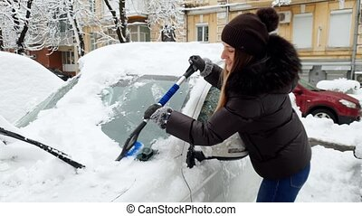 4k footage of smiling young woman cleaning her car from snow...