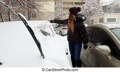 4k footage of smiling young woman cleaning her car from snow before riding to work