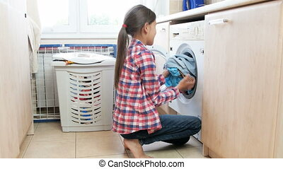 4k footage of teenage girl taking clean clothes out of...