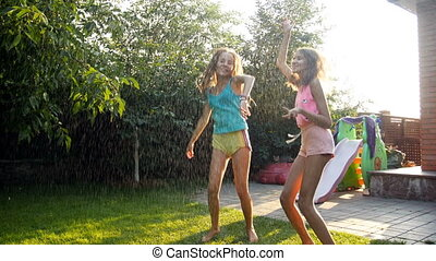 4k footage of two cheerful laughing teenage girls jumping and dancing under rain at house backyard