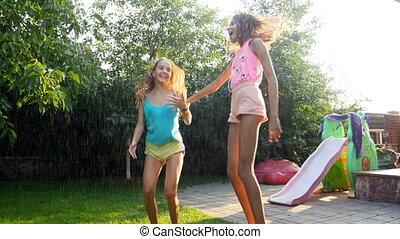4k footage of two teenage girls enjoying rain on hot summer day at backyard