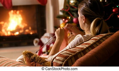 4k footage of woman sitting in armchair at burning fireplace and knitting jumper