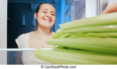 4k footage of young beatiful woman taking and biting celery from refrigerator at night