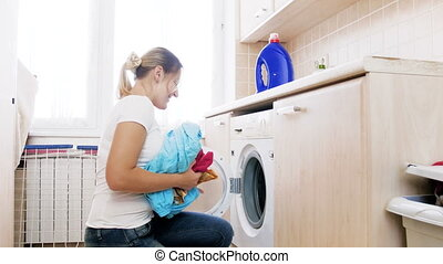 4k footage of young beautiful housewife loading washing machine with dirty clothes