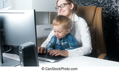 4k footage of young businesswoman working in office with her cute smiling toddler boy