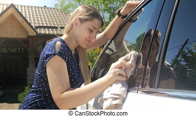 4k footage of young female driver cleaning mirrors and...