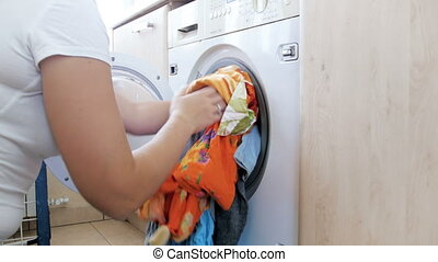 4k footage of young husewife loading clothes in washing...