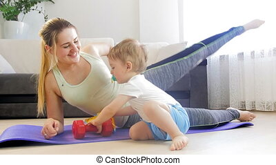 4k footage of young mother exercising on fitness mat at home with her cute baby boy playing on floor