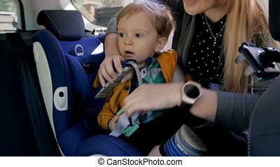 4k footage of young mother fastening seat belts on her...
